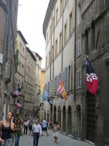 Lorong dengan bendera Contrada adalah pemandangan otentik Siena