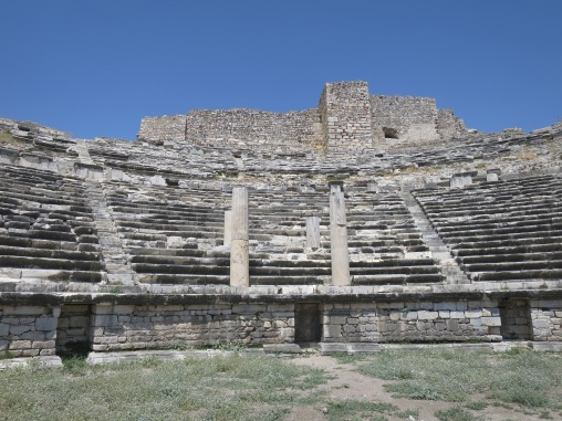 Gedung teater dan kursi VIP dengan tiang di tengah. Bangunan di belakang teater adalah benteng dari zaman Kekaisaran Byzantium