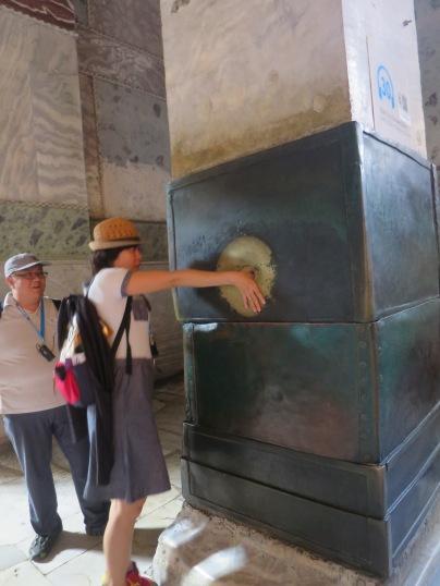 The Wishing Column dan seorang turis tiongkok yang sedang mencoba khasiat pilar ini